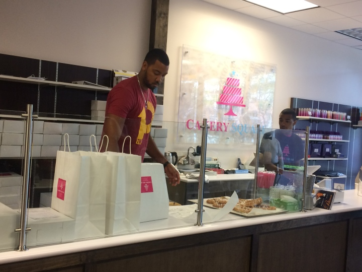 Cakery owner Wesley Lyons prepares a box of doughnuts for a customer.