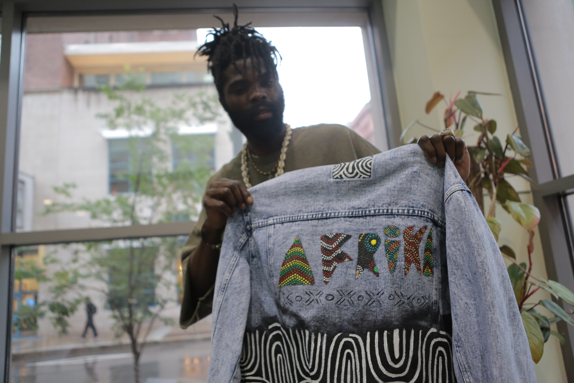 A fashion designer who specializes in Banut fashion shows off one of his designs in his shop in Baldwin, Pa.